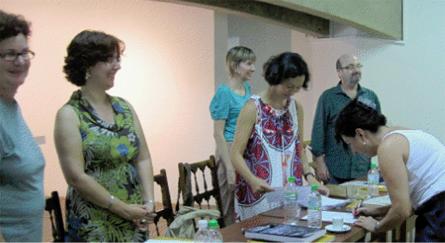 Ana Paula assinando o documento de aprovação em frente à banca de doutores (da esquerda para direita): Luise Weiss, Maria de Fatima Morethy,  Anna Paula Gouveia, Daniela Kurschat e Silvio Dworecki